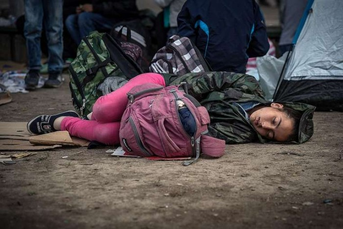A young refugee girl sleeping on the ground.