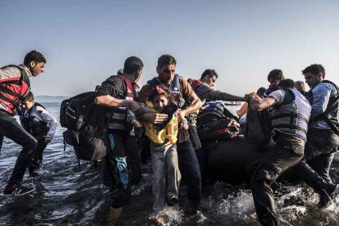 Migrants pulled a boat crowded with Syrians onto the shore at Lesbos.