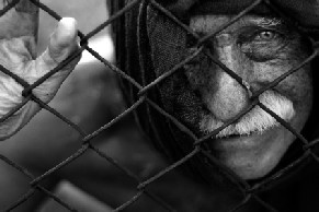 An old man trapped behind a fence