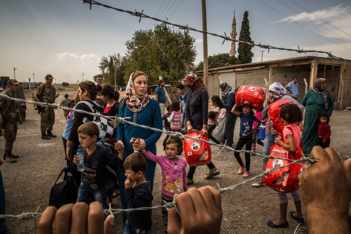 Kurdish women and children from Syria at a Turkish military checkpoint near Kobani