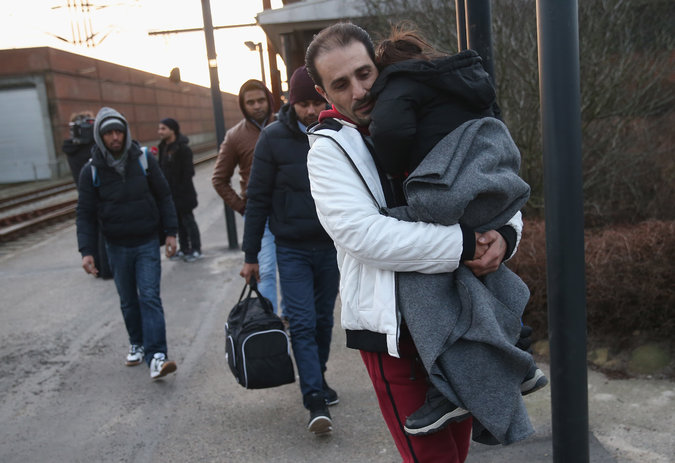 A group of six migrants, including a young child, are walking outside with few belongings