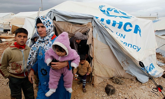 A mother holding her two children in front of a UNHCR tent.