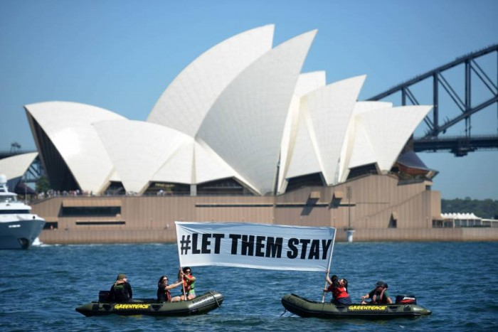 Members of greenpeace staging a protest in Sydney, holding a banner which reads ''#LET THEM STAY''.