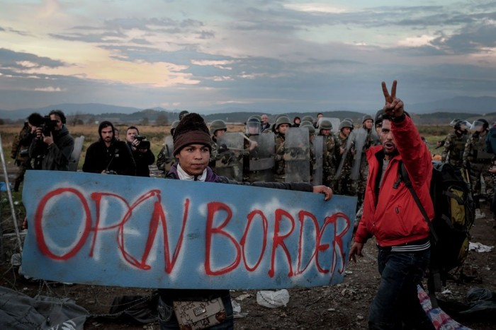 Migrants brandishing a poster reading ''open borders'' in front of security forces.