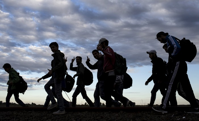 Migrants walking with their backpacks.