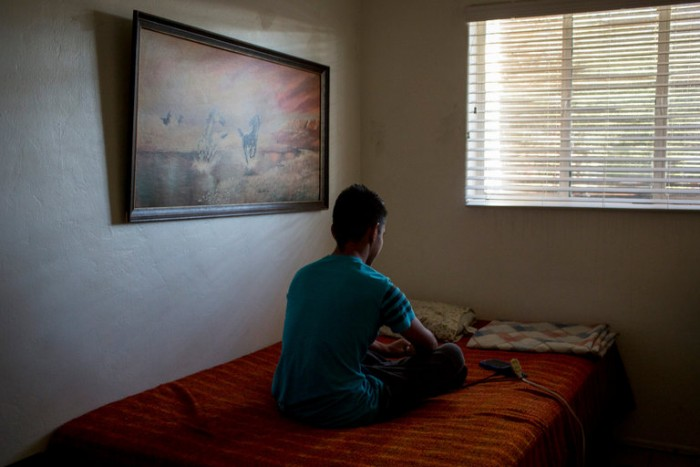 Picture of a 15-year old who fled El Salvador for the United States and now lives with his uncle in Tucson, sitting on a bed.