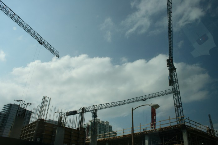 A picture showing three cranes and a building getting constructed