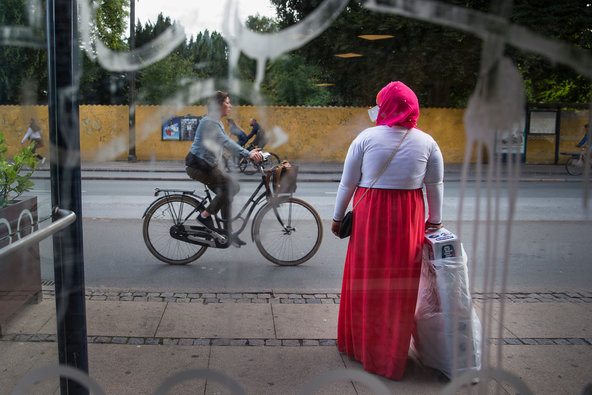 The picture shows a picture of a woman wearing a red hidjab and a long red skirt, waiting for the bus in a multicultural neighbourhood in Copenhagen