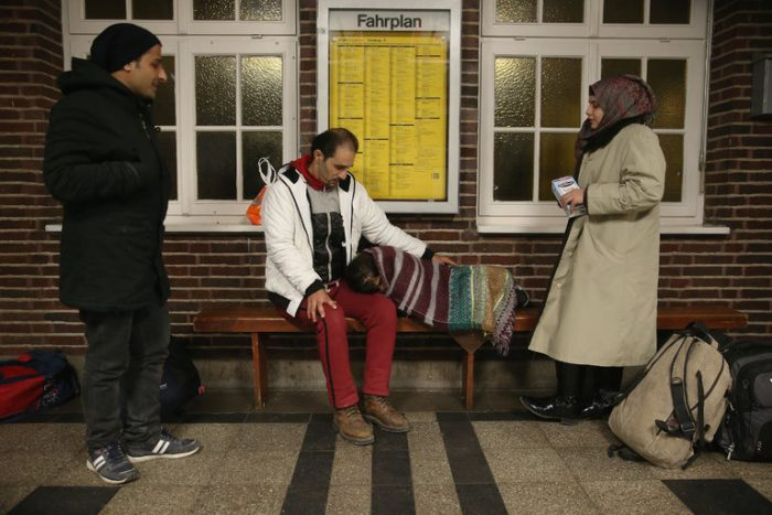 Three refugees waiting in a train station for a train in Germany near the Danish border