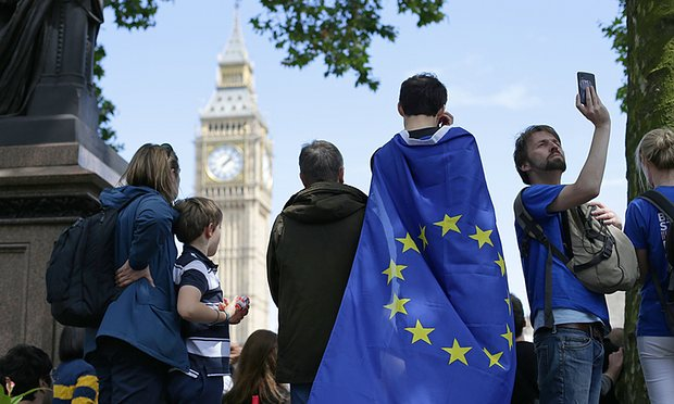 Picture showing a group of people draped in an EU flag, looking at the British Parliament