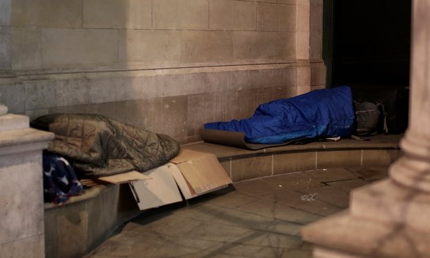 The picture shows homeless people in sleeping bags, outside.