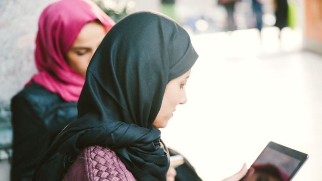Picture shows two women wearing a headscarf and reading.