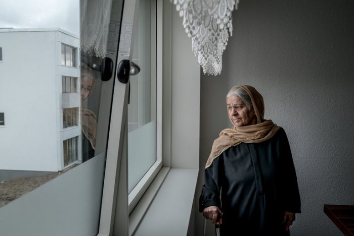 Picture shows Zarmena Waziri, aged of 70 years old, looking through window.
