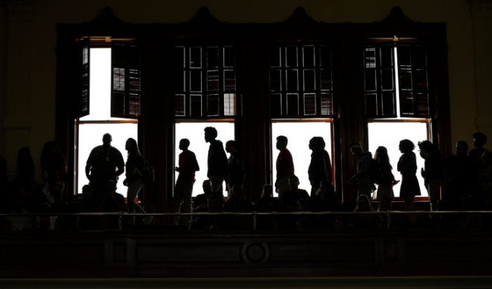Picture showing people walking towards each other in a dark setting.