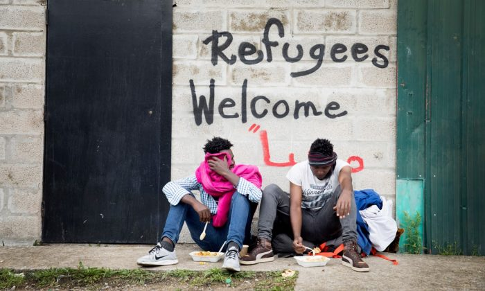 Graffiti says 'Refugees Welcome' on a sign in Calais, France, but the industrial zone where refugees sleep is not a welcoming place. Photo Credit: The Guardian