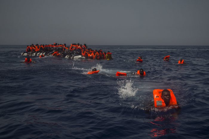 African migrants try to reach a rescue boat from the Spanish NGO Proactiva Open Arms, after falling from the punctured rubber boat in the Mediterranean Sea, about 12 miles north of Sabratha, Libya on Sunday, July 23, 2017. (AP Photo/Santi Palacios)