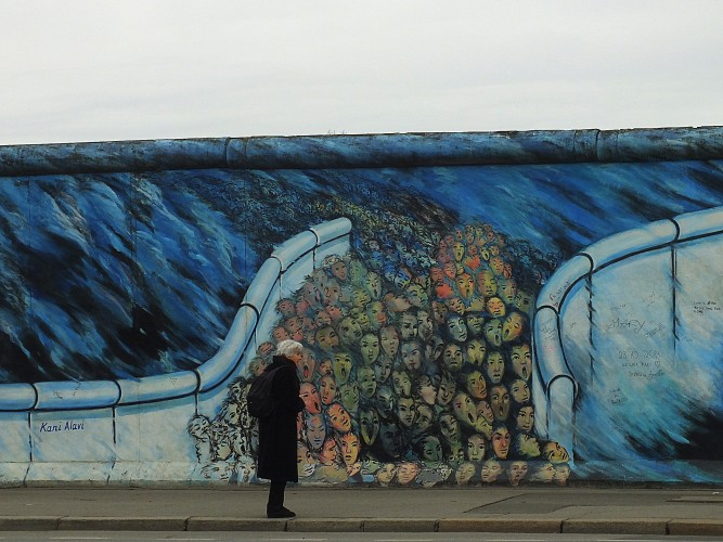 One painting of the East Side Gallery showing faces passing through an open border.