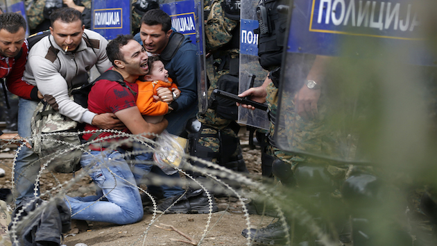 Migrant men help a fellow migrant man holding a boy as they are stuck between Macedonian riot police officers and migrants during a clash near the border train station of Idomeni, northern Greece, as they wait to be allowed by the Macedonian police to cross the border from Greece to Macedonia, Friday, Aug. 21, 2015.