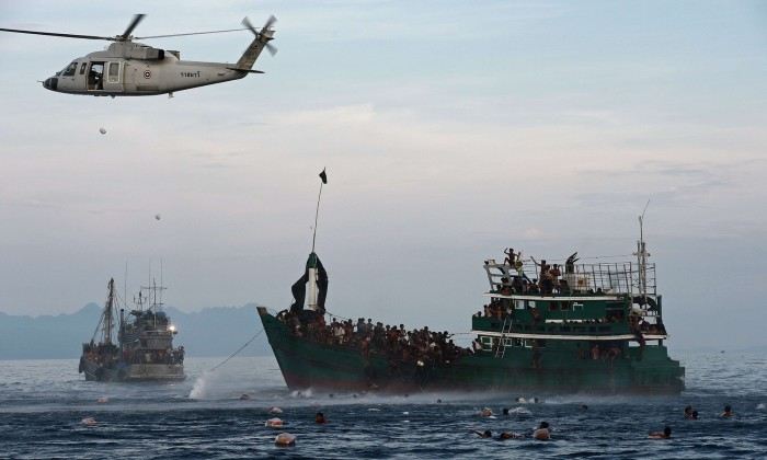 An helicopter is dropping food supplies in the sea where migrants are swimming.
