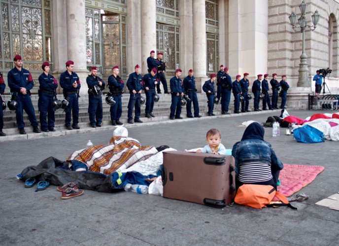 Syrian refugees sleeping on the floor in front of Hungarian police forces.
