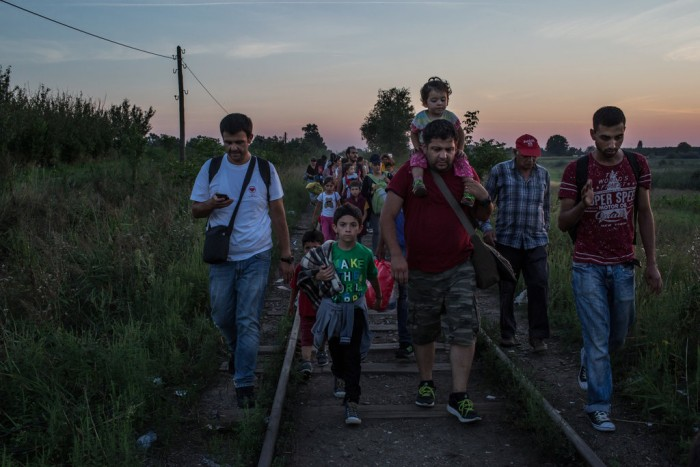 Around 20 people, adults and children, walking on a railroad.