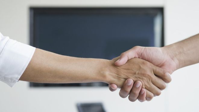 Image of two people shaking hands.