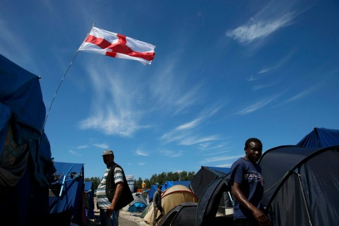 Picture of an English flag flying above a migrant camp in Calais, France, on Friday, after Britain voted to leave the European Union.