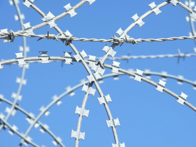 The picture shows a close-up of a razor wire likely found at a border.