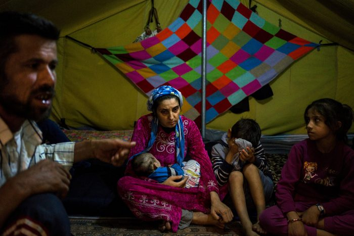 A picture of a mother holding a small child in her arms in a colourful tent in a refugee champ. She is also surrounded by some of her remaining children.