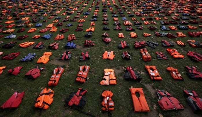 Picture of la few hundred lifejackets displayed on grass to represent the refugees that died trying to reach Europe.