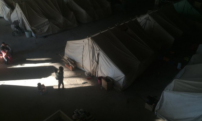 The picture shows tents and children walking in the gloomy warehouse that is a former toilet paper factory.