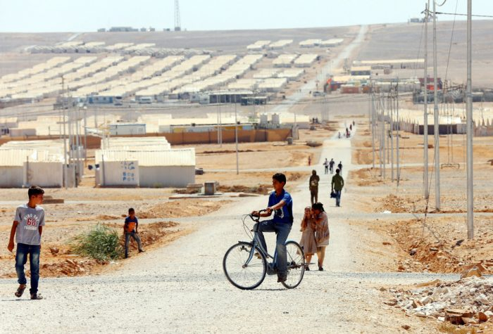 A picture of a young refugee riding a bicycle, in a vast Syrian refugee camp