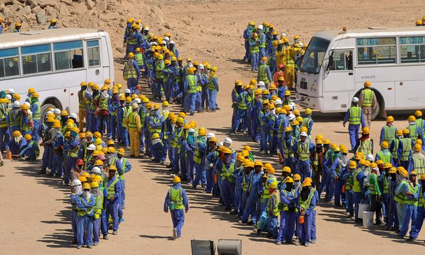 The picture shows a few hundred constructions workers waiting in several lines to get back into buses