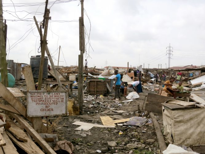 A few people go through a pile of demolished materials, which are their houses.