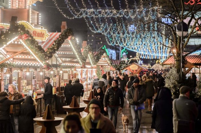 A few people are walking amidst the Christmas market full of lights as it reopened after the attacks