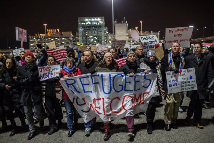 """Picture showing protesters in front of JFK airport, holding banner that reads """"Refugees Welcome"""""""