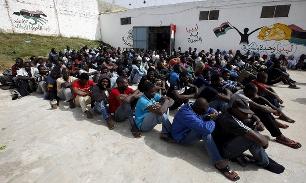 Picture shows a group of migrants sitting outside in a detention center in Tripoli