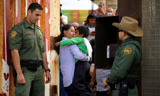 The picture shows a mother holding her child at the US and Mexico border