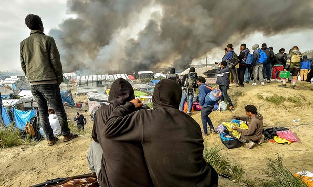 A picture showing two women sitting and looking at the destruction of the Calais camp