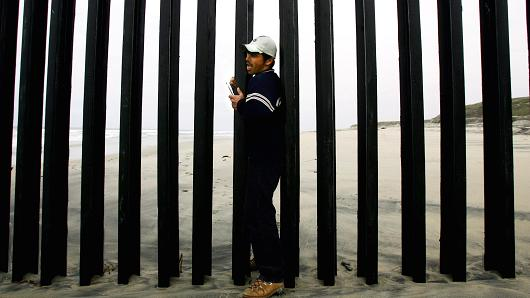 Man trying to walk through the fenced border between Mexico and the United States.