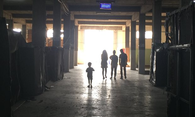 Picture showing four people walking in a refugee camp.