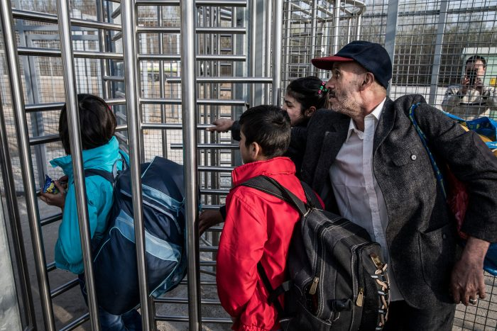 Picture showing four refugees crossing the fenced border between Serbia and Hungary