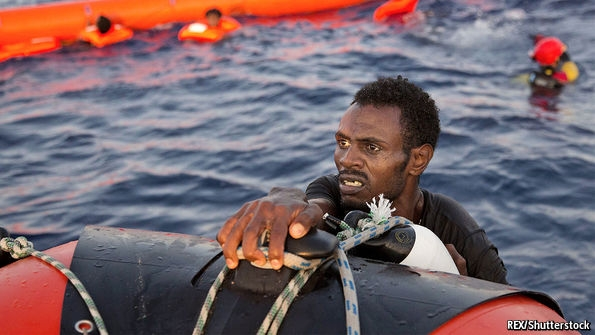 Picture showing a black man at sea, holding on to a life buoy